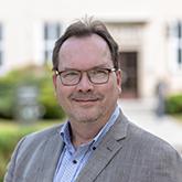 Porträtfoto von Dr. Henning Riecke vor der BAKS
