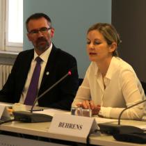Ein geschäftlich gekleideter Mann und eine geschäftlich gekleidete Frau sitzen an einem Tisch; die Frau spricht in ein Mikrofon.
