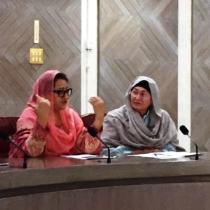 Zwei Frauen in traditioneller islamischer Kleidung sitzen an einem Tisch mit Mikrofonen; eine spricht, die andere blickt zu ihrer Nachbarin.