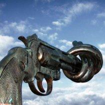Das Bild zeigt einen Revolver mit Knoten im Lauf vor hellem Himmel.