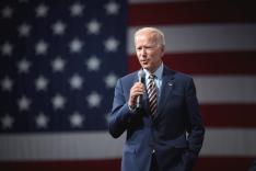 Joe Biden steht mit einem Mikrofon in der Hand vor einer großen Flagge der USA.