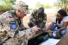 a German EUTM Mali soldier, supported by an interpreter, teaches a Malian soldier in explosive ordnance disposal