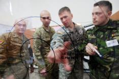 Vier Männer in militärischer Uniform stehen vor einer beschrifteten Glaswand und deuten mit ihren Händen darauf..