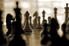 Schwarze und weiße Schachfiguren stehen auf einem Schachbrett.