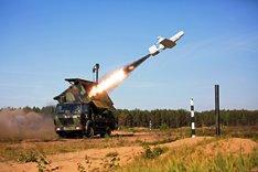 Ein gepanzertes Fahrzeug in Flecktarn schießt eine Drohne in die Luft.