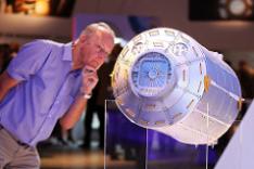 Ein Mann schaut auf ein zylinderförmiges Metallobjekt, das offenbar ein Modell eines in der Realität größer ausfallenden Industrieprodukts darstellt.