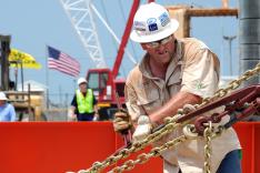 Ein Mann in Arbeitskleidung und Schutzhelm hantiert mit Werkzeug an einer gespannten Kette; im Hintergrund weht eine US-amerikanische Flagge, und weiteres Arbeitsgerät ist zu sehen.