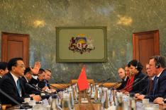 Menschen sitzen um einen Konferenztisch; in der Mitte steht eine Flagge der Volksrepublik China
