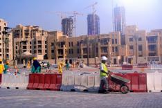 Im Vordergrund sind zahlreiche arbeitende Bauarbeiter zu sehen; im Mittelgrund ragen mehrstöckige Gebäude im Rohbau, im Hintergrund Hochhäuser im Rohbau auf.