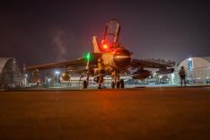 Ein Kampfflugzeug vom Typ Tornado steht bei Nacht auf einem beleuchteten Vorfeld zwischen zwei Hangars.