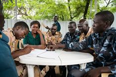 Mehrere Menschen in Uniform sitzen um einen Tisch und diskutieren.