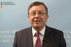 Porträtfoto von Brigaqdegeneral a.D. Armin Staigis vor einer blauen Wand mit der Aufschrift BAKS Bundesakademie für Sicherheitspolitik und einer Bildwortmarke der BAKS