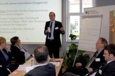 Die Teilnehmerinnen und Teilnehmer des Methodenseminars Strategische Vorausschau sitzen in einer Arbeitsgruppe zusammen und diskutieren; ein Mann hält stehend einen Vortrag.