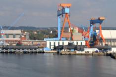 Auf einem Werftgelände am Wasser liegen mehrere Unterseeboote im Bau an Land; darüber ragen große Werftkräne auf.