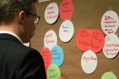 Ein Mann blickt auf eine Pinnwand, an der viele farbige und beschriebene Zettel in Gruppen angebracht sind.
