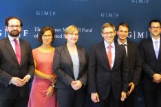 Mitglieder des Arbeitskreises Junge Sicherheitspolitiker stehen gemeinsam mit Derek Chollet vor einer Pressewand des German Marshall Fund in Berlin.