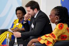 Zwei traditionell afrikanisch gekleidete Frauen und ein geschäftlich gekleideter Mann sitzen gemeinsam auf einem Podium.
