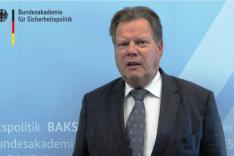 BAKS-Präsident a.D. Rudolf Adam steht vor einer blauen Pressewand der BAKS.