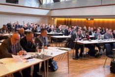 Männer, darunter einige in militärischer Uniform, sitzen in einem großen Saal an langen Tischen.