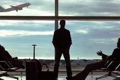 Zwei Personen, eine stehend, die andere sitzend, im Wartebereich eine Flughafens. Durch die Großen Fenster sieht man ein startendes Passagierflugzeug.