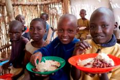Eine Gruppe afrikanischer Kinder sitzt mit gefüllten Tellern in den Händen in einem Gebäude aus weidengeflechtartigen Holzwänden und blickt zum Betrachter.