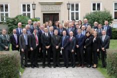 Eine Gruppe geschäftlich gekleideter Menschen, links im Bild ein militäruniformtragender Mann steht vor dem Haus Bonn der BAKS.