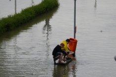 Zwei Kinder sitzen auf einer Bank von Hochwasser umgeben.