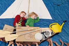 Zwei Jungen sitzen in einem selbstgebauten Boot, werden von vielen Händen getragen.