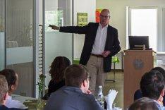 Christian Lipicki hält neben einem Pult stehend einen Vortrag vor Studierenden an der BAKS.