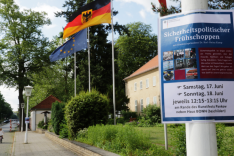 """Vor dem Haus Berlin der BAKS wehen die Flaggen der EU, Deutschlands und Berlins; an einem Laternenmast recht hängt ein Plakat mit der Aufschrift """"Sicherheitspolitischer Frühschoppen""""."""