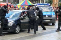 Vermummte und bewaffnete Polizisten  öffnen ein Auto mit einer Person darin