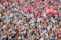 Das Bild zeigt eine beieinander stehende Menschenmenge, deren eine Hälfte als Fans der deutschen Fußball-Nationalmannschaft, die andere als Fans der türkischen Fußball-Nationalmannschaft erkennbar ist.