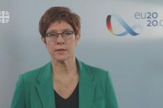 Annegret Kramp-Karrenbauer spricht vor einer hellblauen Wand zum Zuschauer.