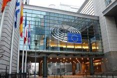 Ein großes Gebäude mit Fensterfront ist zu sehen, davor etliche Flaggen und die eine Bronze Skulptur