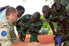 Ein deutscher Soldat spricht hockend mit drei malischen Soldaten und einem Übersetzer.