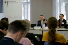 Zwei Herren im Anzug, der linke gestikulierend und in ein Mikrofon sprechend, sitzen in einem Seminarraum gegenüber einer Gruppe von Menschen.