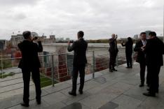 Mehrere Menschen stehen Smartphones in der Hand haltend auf der Dachterrasse des Bundeskanzleramts in Berlin und blicken fotografierend zum Reichstag hinüber.