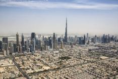 Betrachtet aus der Vogelperspektive ragen zahlreiche Hochhäuser in einem wüstenartigen Gebiet neben einem Wohnviertel in den Himmel auf.