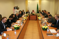 Das Foto zeigt Menschen in arabischer und westlicher Kleidung, die an einem großen Konferenztisch sitzen.