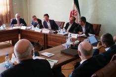 Zahlreiche geschäfftlich gekleidete Menschen Sitzen um einen viereckig zusammengestellten großen Tisch und sprechen miteinander; hinter dem Tisch steht eine Fahne des Iran; von links fällt Licht durch ein Fenster mit Vorhängen davor.