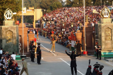 Beiderseits eines Grenztores sind verschieden gekleidete Soldaten aufmarschiert und halten ein Zeremoniell ab. Die Szenerie wird durch hunderte Zuschauer auf einer Tribüne verfolgt.