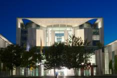 Das Bild das Gebäude des Bundeskanzleramts in Berlin bei Nacht, angestrahlt durch Scheinwerfer und mit mehreren Bäumen davor.
