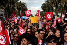 Auf einer Straße gesäumt von Palmen steht eine große Menschenmenge, die zahlreiche Flaggen Tunesiens und Plakate in arabischer Sprache mit sich führt.