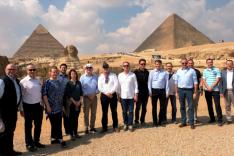 Eine Menschengruppe steht vor den Pyramiden und der Sphinx in Giseh, Ägypten.