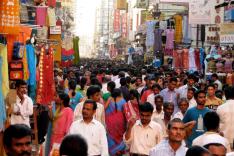 Zahlreiche Menschen drängen sich durch eine überfüllte Marktgasse in Indien