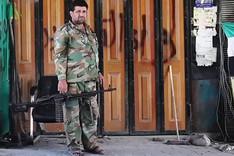 """Ein Kämpfer der """"Freien Syrischen Armee"""", bewaffnet mit einem Maschinengewehr, vor einer verschlossenen, mit Graffiti besprühten, Ladenfront."""