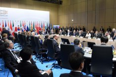 """Zahlreiche Außenminister der G20-Mitgliedsstaaten sitzen um einene großen Konferenztisch vor einer Pressewand mit der Aufschrift """"G20 Germany""""."""