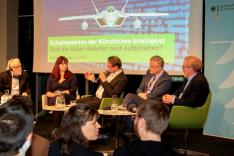 """Fünf Menschen sitzen gemeinsam und diskutieren auf einem Podest; im Hintergrund zeigt eine Leinwand ein Flugzeug und die Schrift """"Schattenseiten der Künstlichen Intelligenz""""."""