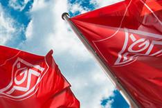 Flaggen der IG Metall vor blauem Himmel