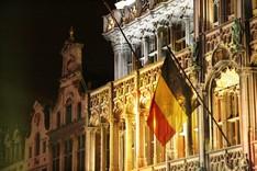 An einer Gebäudefassade weht die Nationalflagge Belgiens